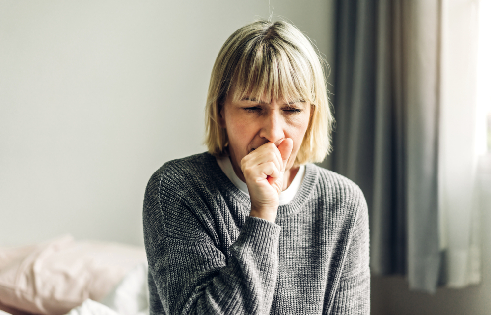 woman coughing into fist